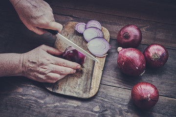Chef chopping a red onion with a ceramic knife on the cutting board