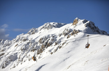 Snow-capped mountains. Alps, winter landscape. Ski resort. Chair lift. Bellamonte, Lusia, Valbona, Dolomites, Italy, Trentino. Winter mountains,panorama - snow-capped peaks of the Italian Alps