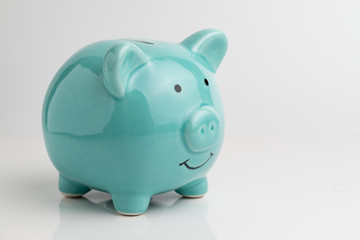 Blue piggy bank on reflection floor and seamless white background