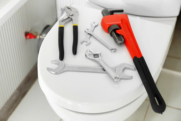 Plumber's tools on toilet seat lid