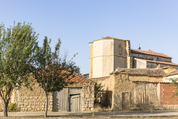 ancient houses made of clay and the church in Castrillo Mota de Judios village, province of Burgos, Spain