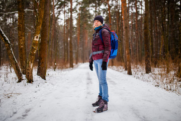 Side view of girl in hat with backpack over winter forest