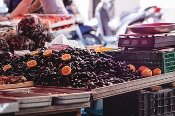 Stall at the fish market with mussels garnished with lemons in a southern Italian market