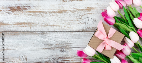 springtime pink tulips on white rustic wooden boards for Mothers Day or Easter concept