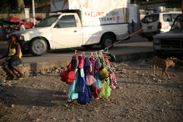 Costumes hang on a rope at a stand in a street of Port-au-Prince