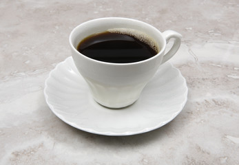 White cup of coffee on marble countertop