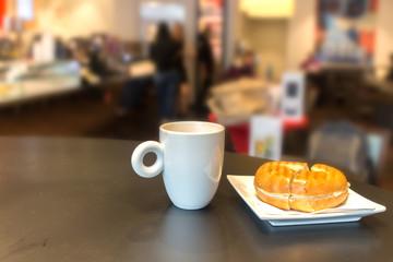 A mug with coffee and a sandwich on a table