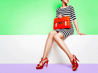 Woman holding orange bag and red heels shoes sitting on the bench. Spring fashion image.