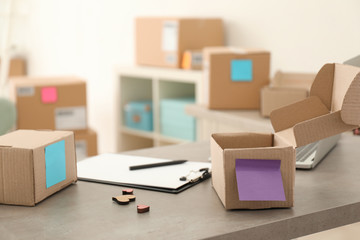 Preparing parcels for shipment to customers on table in home office. Startup business