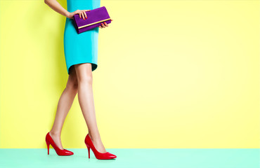 Beautiful legs woman walking with red heels shoes. Isolated on yellow background. Spring fashion image.