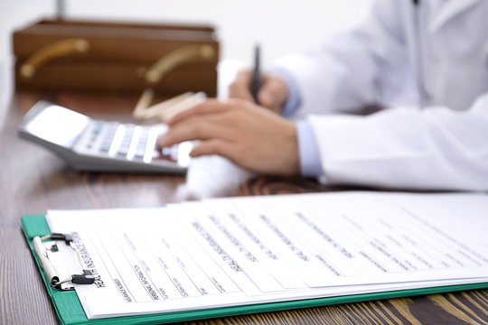 Clipboard with health insurance forms and  doctor at table