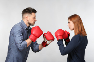 Angry couple in boxing gloves on light background