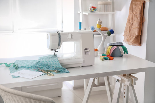 Sewing machine with fabric on table in tailor workshop