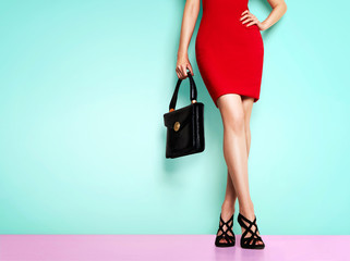 Wall Mural - Beautiful legs woman wearing red dress, black shoes and handbag standing against light blue wall. isolated. Business woman fashion image.