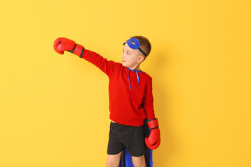 Wall Mural - Cute boy in superhero costume on color background
