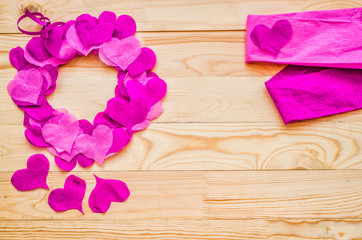 valentine day concept. a wreath decorated with purple and pink crepe paper hearts with pink paper with copy space