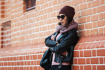 Young fashion woman in black leather jacket leaning on brick wall