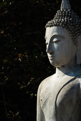 Old cement Buddha image in light and shadow in Autthaya Buddhist ruined temple, travel destination