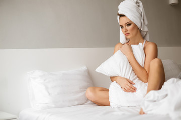 Portrait of beautiful pensive lady sitting in bed with towel on her head and thoughtfully looking aside while hugging white pillow isolated