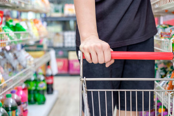 Customer with shopping cart choosing product in store