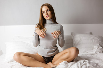 Portrait of young pretty woman in gray sweater sitting in bed and thoughtfully looking aside isolated