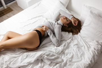 Portrait of  beautiful woman in sweater and black lingerie lying in bad and thoughtfully looking in camera isolated