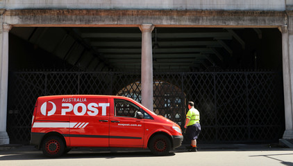 An Australia Post worker walks to his van in Sydney