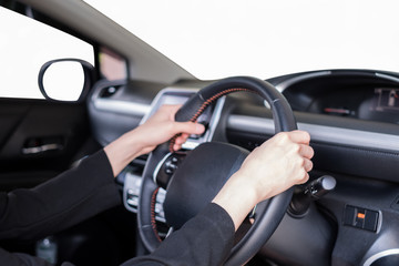 Hand holding steering wheel in modern private car with blank windshield
