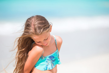 Little girl at beach during caribbean vacation. Portrait of beautiful kid background blue sky