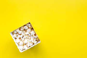 Popcorn in paper bag on yellow background top view copy space