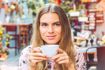 Beautiful woman is enjoying a cup of coffee in the cafe