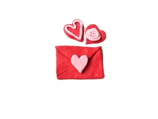 Red envelopes and couple red hearts made from plasticine clay placed on white background, cute Valentine gift dough