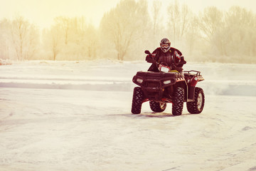 Quad bike driver riding over a frozen lake