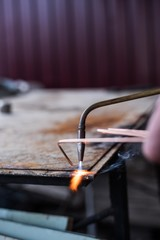 A man welds a metal with a gas burner
