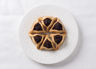 Traditional sweets for Jewish holiday of Purim. Hamantashen cookies or Aman ears, triangular cookies with poppy seeds, top view