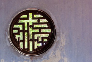 round open wooden window with buddhist design and symbols  with view into a garden