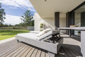 Grey wooden deckchair on patio