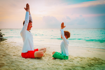 father and son doing yoga at sunset beach