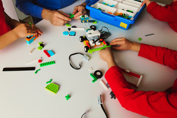 kids and teacher building robot at robotic technology school lesson