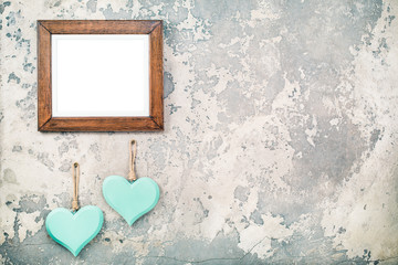 Photo or picture frame blank and pair of handmade Valentine's day love hearts hanging on vintage aged grunge textured concrete wall background. Retro old style filtered photo