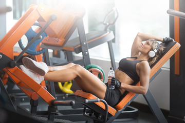 Fitness girl with headphones listening  music in the gym