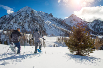 Run with snowshoes. a couple has fun in the mountains