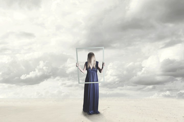 surreal woman with blue dress with hidden face holding a frame of an empty framework in a sea landscape