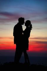Silhouette of a loving couple against the sky after sunset