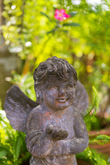 Cute stone angel cupid sculpture with wings decorating the garden
