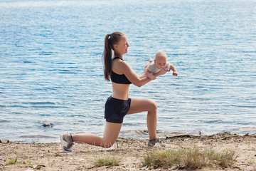 Young mother in the morning near the river doing sports exercises with a baby in her arms