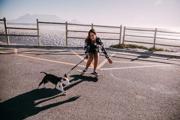 Young woman on skateboard with puppy running along