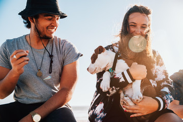 Happy young adult couple with cute puppy