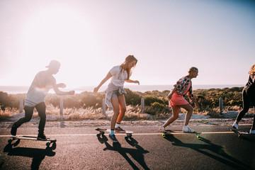 Group of hipster friends longboarding on the road in summer Fotoväggar
