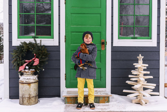 Boy standing outside a house holding a chicken